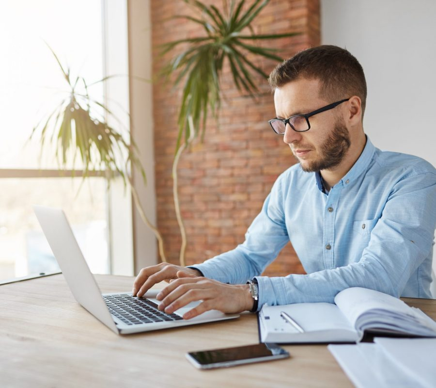 Freelance, business concept. Mature unshaven male freelance web designer sitting in co-working space, working on laptop computer, writing down tasks in notebook, waiting for customer call