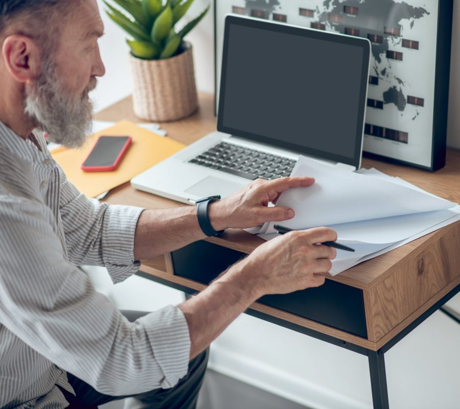 Work from home. A mature businessman working from home and scrutinizing the documents